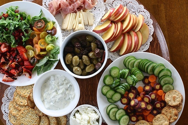 several different plates of fruit and vegetables, and crackers for an appetizer party