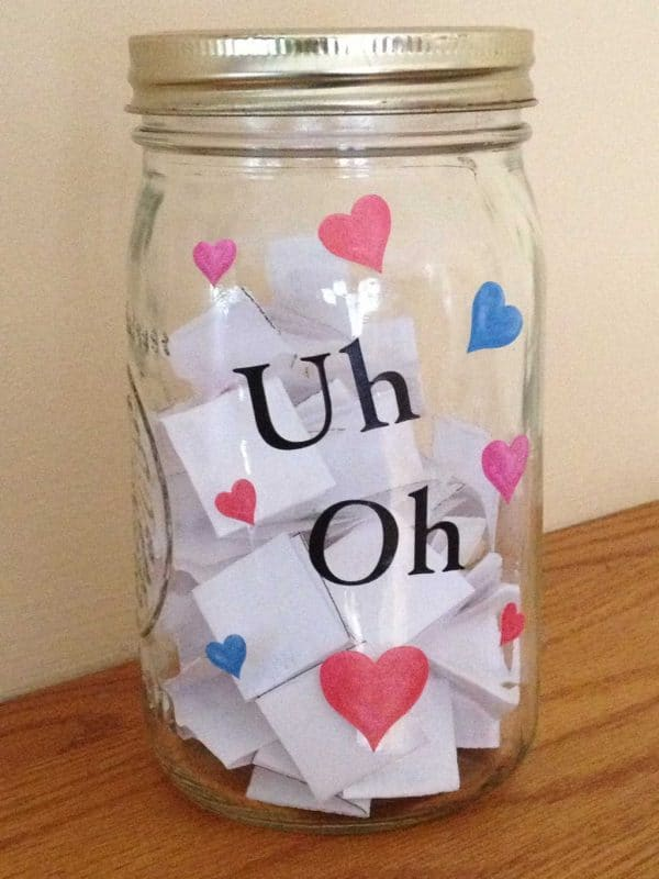 a mason jar with pink, blue and red hearts on it and the words Uh Oh on a brown table