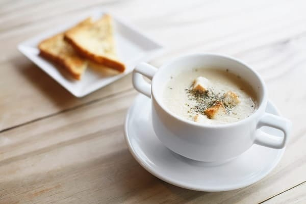 soup in a white bowl next to grilled cheese sandwich on a plate