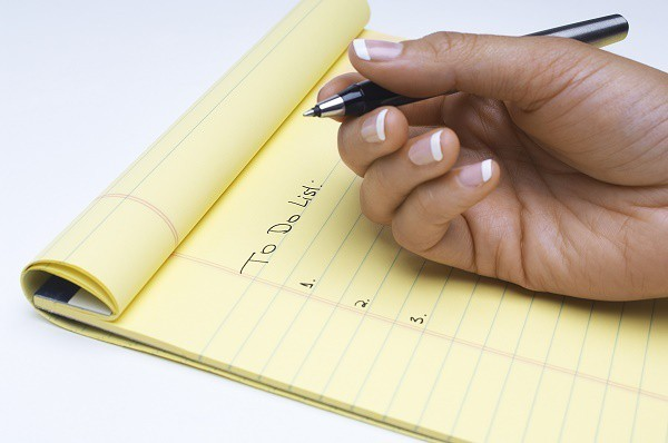 a hand holding a pen on a yellow pad of paper reading To Do List