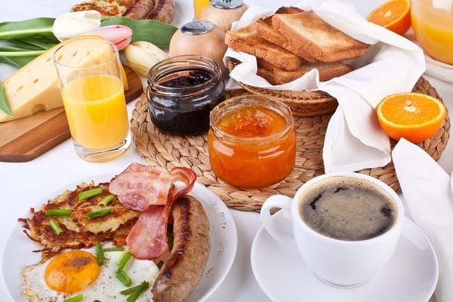 brunch items on several plates on a table, including eggs, bacon, sausage, toast, jams, orange juice, coffee, cheese, sliced oranges