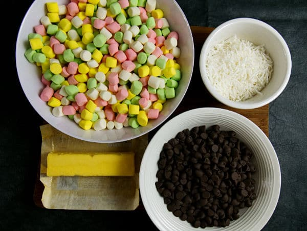 white bowls full of colored marshmallows, shredded coconut, chocolate chips, and a stick of butter