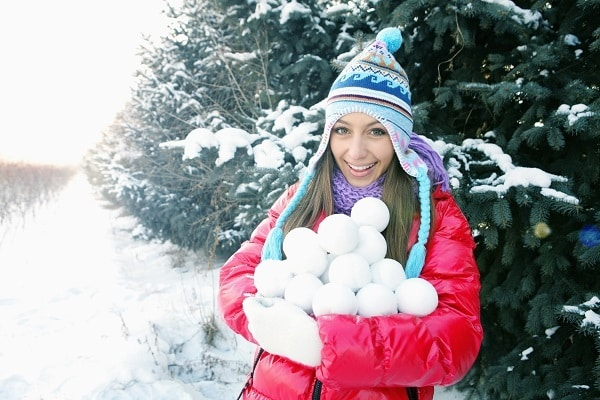 a girl holding a stack of snowballs with trees in the background