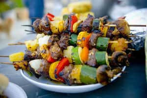 kabobs from the grill on a white plate sitting outside
