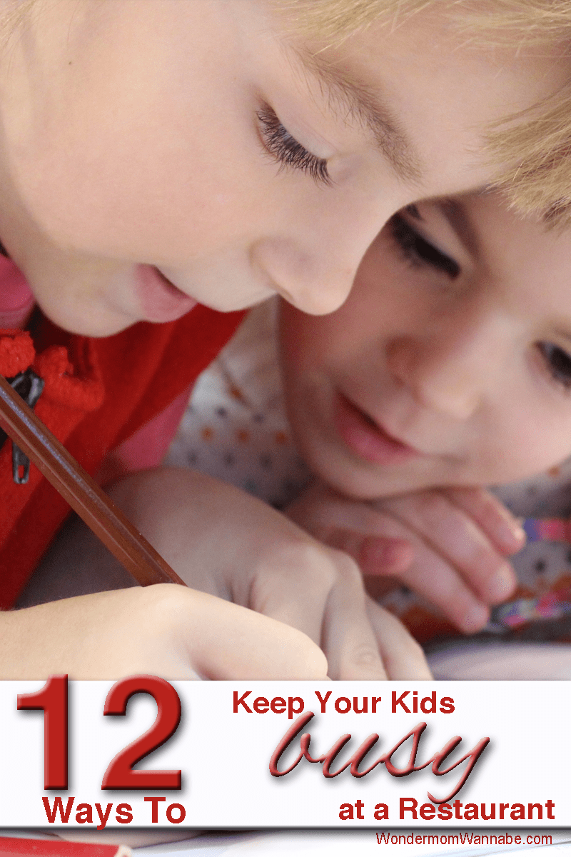 two boys intently looking at a paper with title text reading 12 Ways to Keep Your Kids busy at a Restaurant