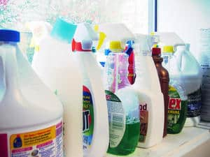 several bottles of cleaners on a windowsill