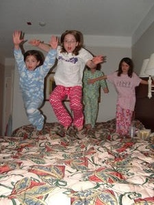 slumber party. 4 girls jumping on the bed