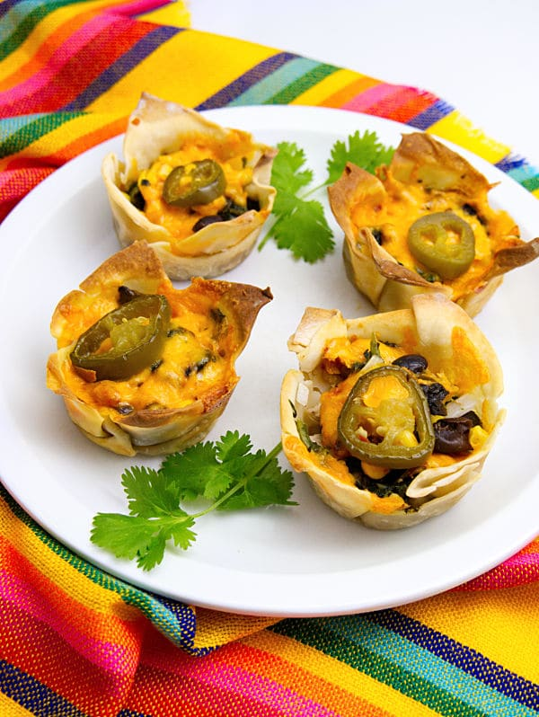 Chicken Enchilada Cups on a white plate on a multi-colored striped cloth