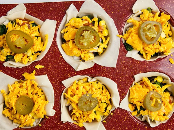 chicken enchilada cups in a muffin tin ready to be baked