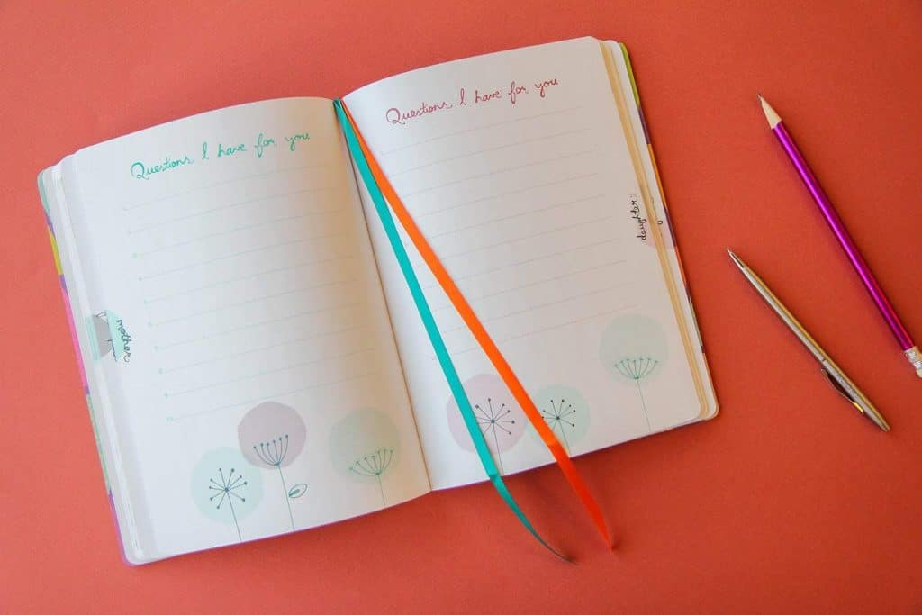 a mother/daughter journal next to a pen and pencil on an orange background