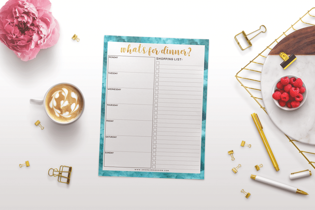 a printable What's for Dinner menu planner and shopping list next to binder clips, coffee in a mug, a pink flower, pens, a tray with a bowl of raspberries on it, all on a white background