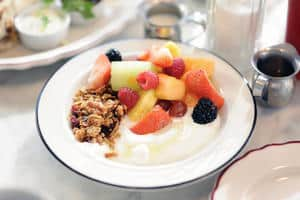 yogurt in white bowl with fruit and granola on top