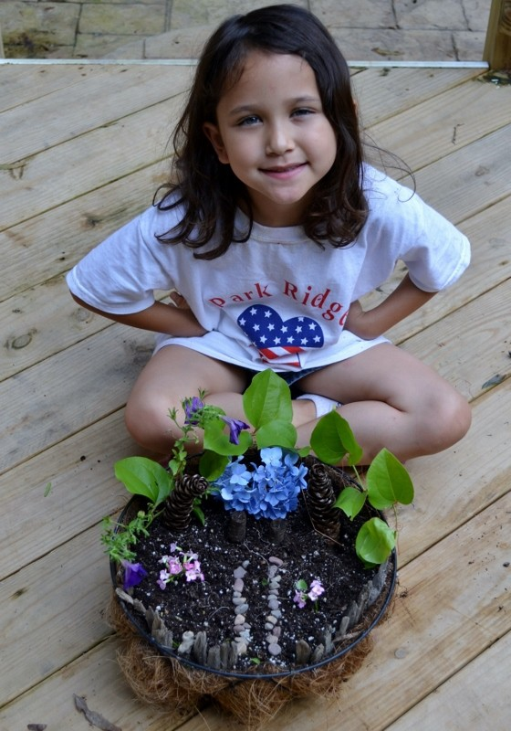 a girl sitting outside on a deck next to a fairy garden that she made