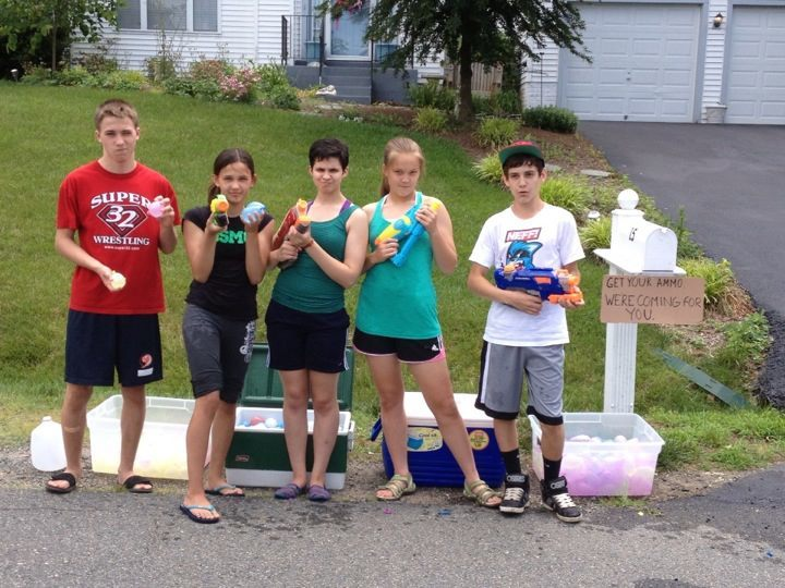 a group of kids holding water balloons, squirt guns, and nerf guns outside