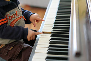 little hands playing keys on piano