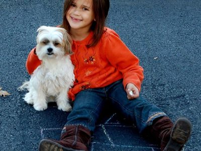 little girl holding puppy dog outside