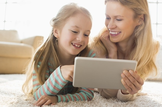 a mom and daughter laying on the carpet looking at a tablet together