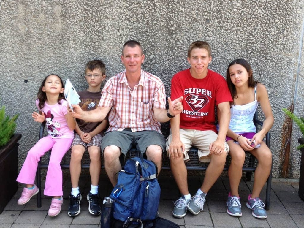 a family sitting on a bench showing their Quest Fun