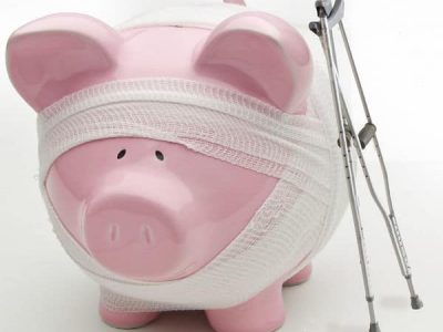 Piggy bank wrapped in gauze and crutches next to it