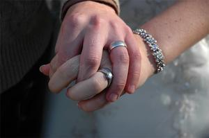 Man and woman holding hands, showing wedding rings