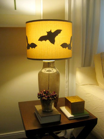 Bat lamp silhouette sitting on side table with books and glass of flowers