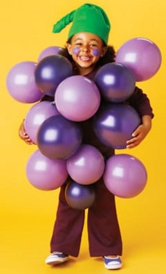 a child dressed in a Grape Costume made out of purple balloons