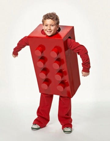 a boy wearing a red Lego Costume made out of a cardboard box