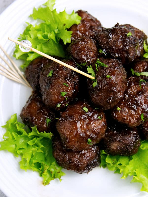 overhead view of meatballs on lettuce on a plate with a toothpick in one of the meatballs