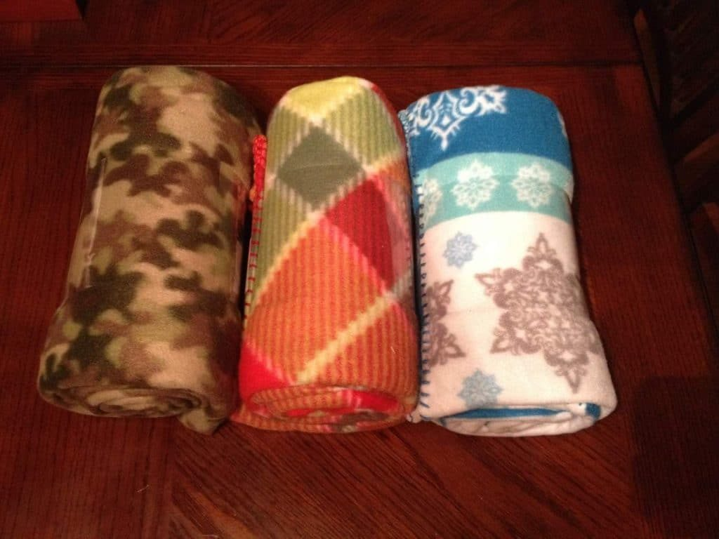 three fleece throws rolled up on a dark brown background