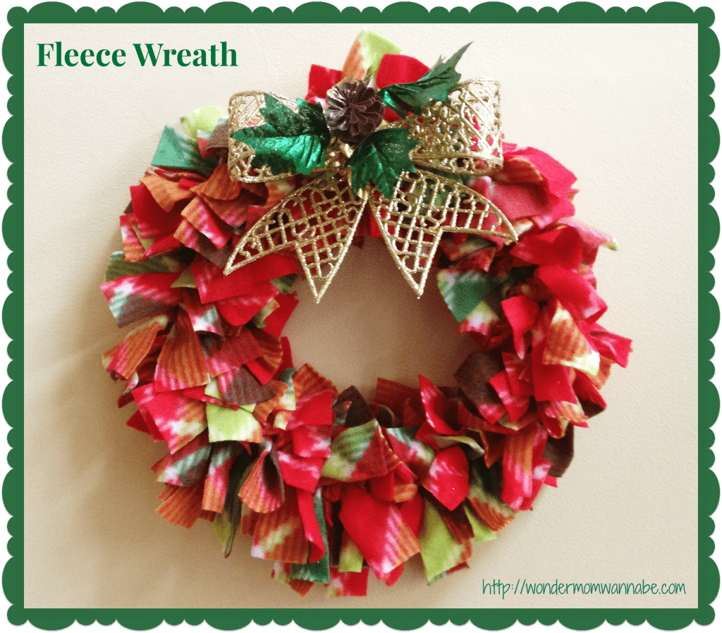 a wreath made out of red and green fleece with a gold bow and title text reading Fleece Wreath