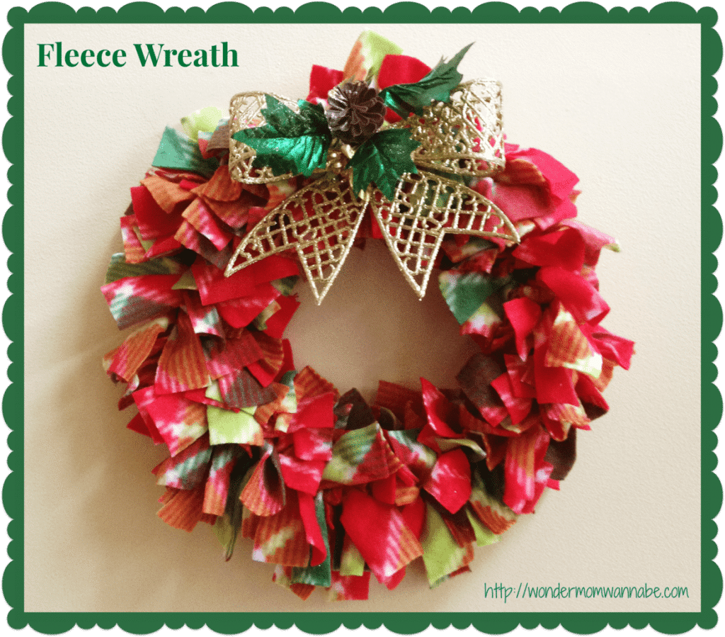 a wreath made out of red and green fleece with a gold bow with title text reading Fleece Wreath