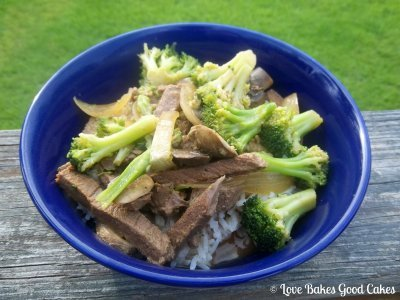 Crockpot Beef and Broccoli in a blue bowl on a wood table outside