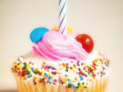 Vanilla cupcake with colored sprinkles, pink frosting and a blue and white striped candle on fire