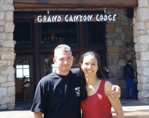 a husband and wife in front of the Grand Canyon Lodge