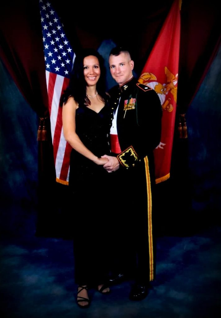 a husband and wife dressed up at a Marine ball in front of the American flag and Marine flag