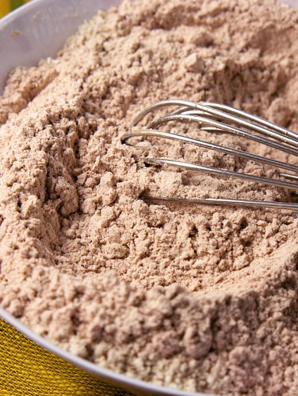 dry ingredients for the cookies in a bowl with a whisk in it