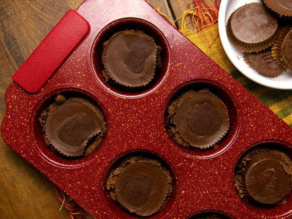 peanut butter cups on top of cookie dough in a red muffin tin