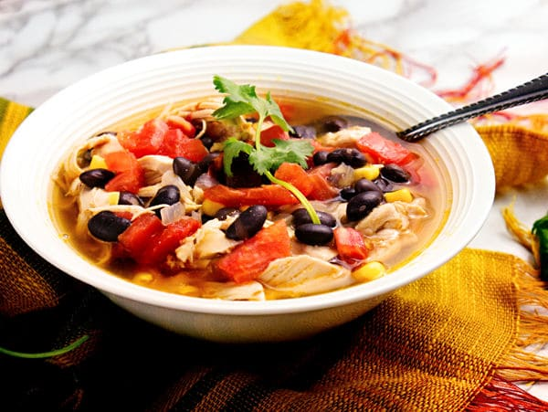 tex mex chicken soup in a white bowl with a spoon in it