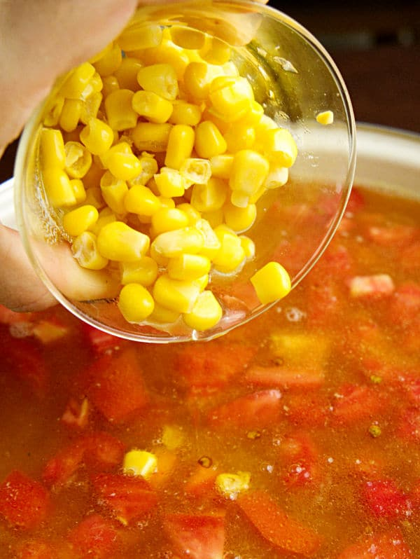 corn kernels being added to the tex mex chicken soup in a pot