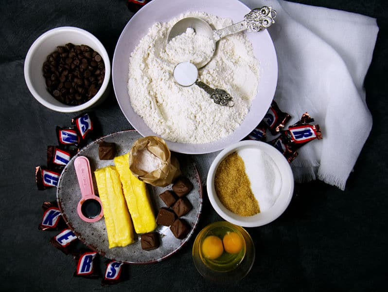 ingredients in bowls needed to make Snickers Surprise Cookies