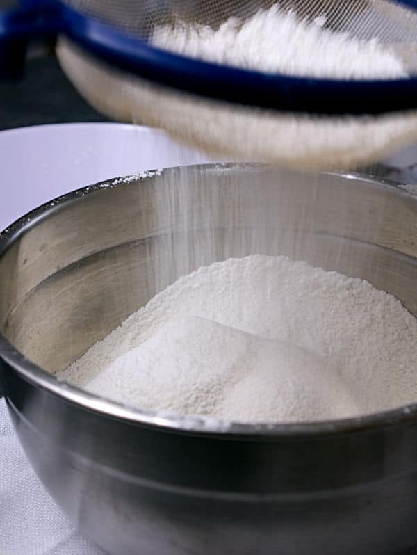 flour and baking soda being sifted into a metal mixing bowl
