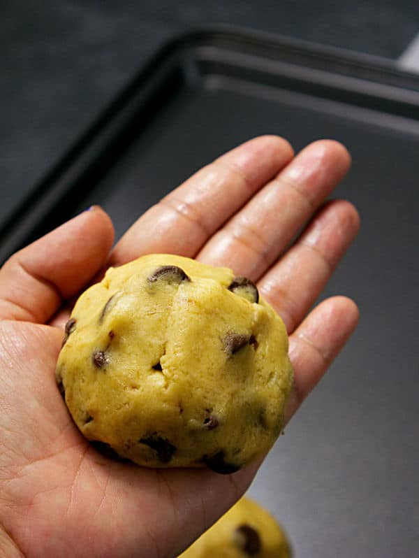 a hand holding cookie dough with a snickers bar inside of it