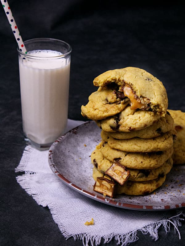 a stack of Snickers Cookies on a plate next to a glass of milk