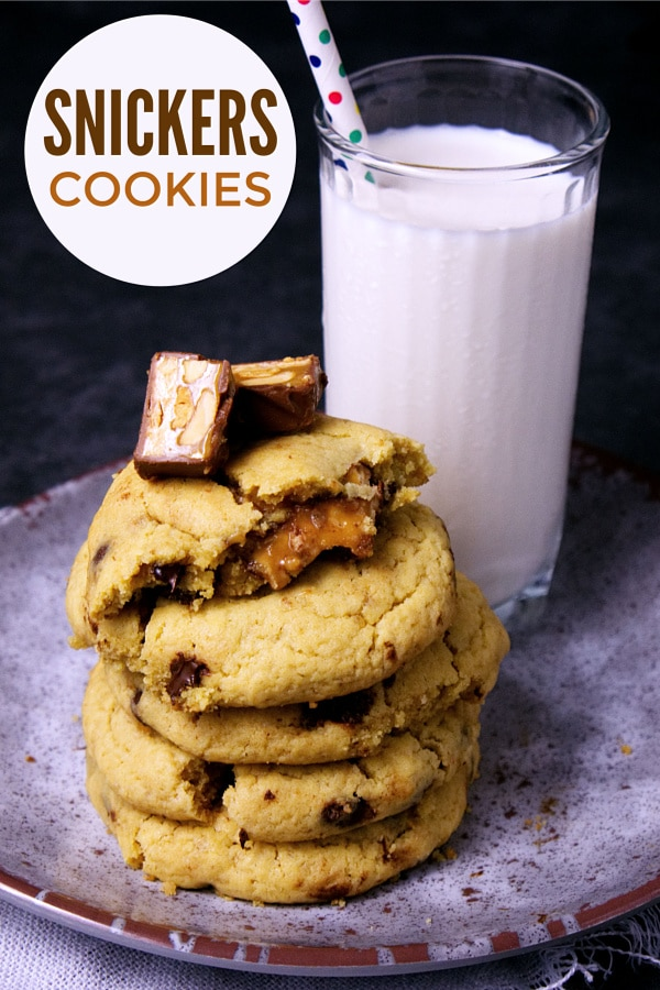 A stack of cookies next to a glass of milk on a plate with title text reading Snickers Cookies