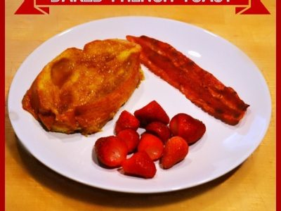 Baked french toast with a piece of bacon and cut up strawberries on white plate