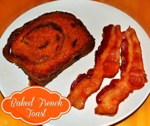 Cinnamon Raisin Baked French Toast next to two slices of bacon on a white plate