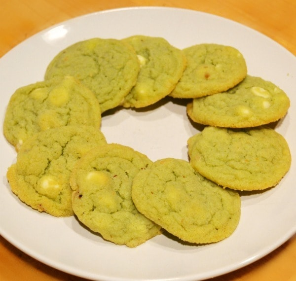 Pistachio Cookies on a white plate on a brown table
