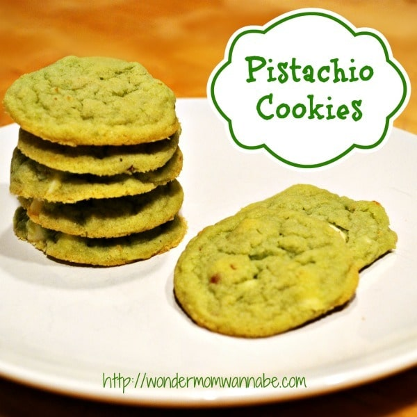 a stack of pistachio cookies on a white plate on a brown table with title text reading Pistachio Cookies