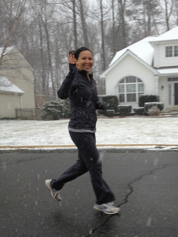 Woman jogging in the snow and waving at camera