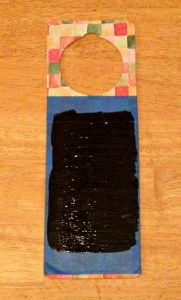 a door hanger with painter's tape and black paint on it